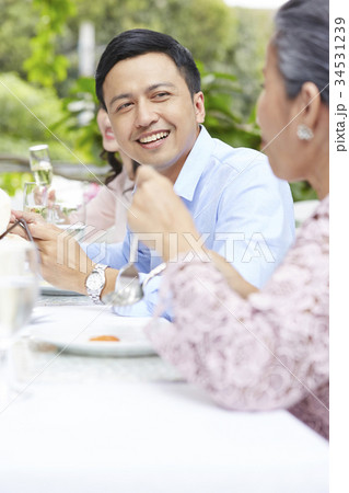 a handsome man is talking with his mother when eating 34531239