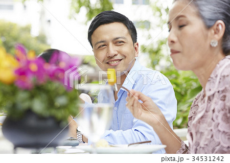 a healthy man is looking his mother while having breakfast in a restaurant 34531242
