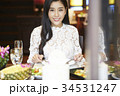 a woman with floral shirt is smiling and eating in a luxurious restaurant 34531247