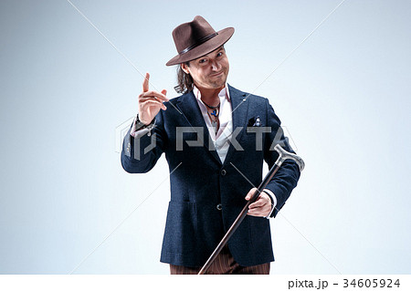 the mature man in a suit and hat holding cane の写真素材 34605924
