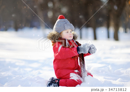 Little boy in red winter clothes having fun with snow 34713812