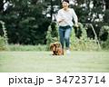 犬と走る若い女性 ミニチュアダックスフント 34723714