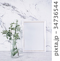 Blank frame and white flowers over marble table 34736544