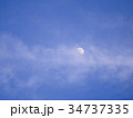 Half moon over the moving clouds 34737335