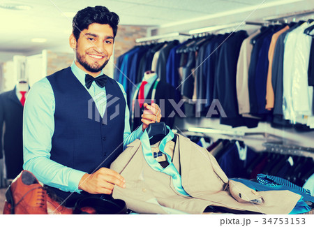 Man demonstrating suit in shop 34753153