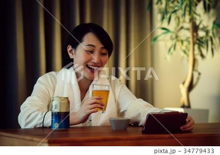 宅飲み スマホで動画を見る女性 34779433