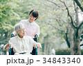 公園を散歩するシニアとヘルパー 車椅子 34843340