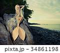 Beautiful mermaid sitting on rock 34861198