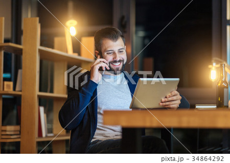 Happy brunette looking at his tablet 34864292