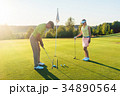 Man ready to hit the golf ball while exercising 34890564