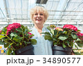 Portrait of an active senior woman holding two 34890577