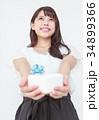 プレゼントボックスを渡す若い女性 34899366