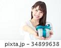 プレゼントボックスを渡す若い女性 34899638