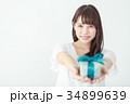プレゼントボックスを渡す若い女性 34899639