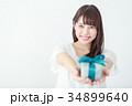 プレゼントボックスを渡す若い女性 34899640