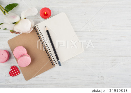 Blank notebook, pink macaroons, lit candleの写真素材 [34919313] - PIXTA