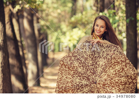 Young  girl smiling in autumn with umbrella 34978080