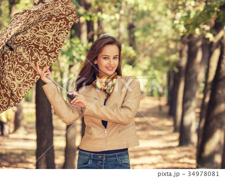 Young  girl smiling in autumn with umbrella 34978081