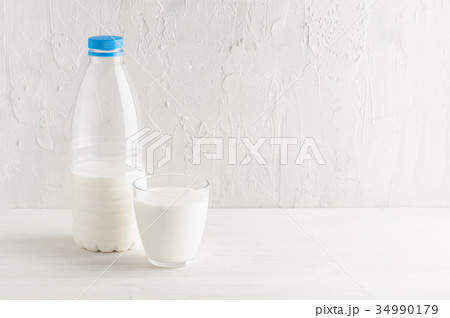 Milk bottle and glass with milk on the white tableの写真素材 [34990179] - PIXTA