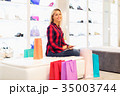 Young woman using a tablet computer in the fashion store 35003744