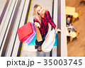 Young woman with shopping bags on escalator in the fashion store 35003745