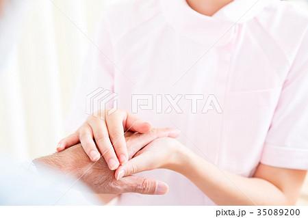 若い看護師とおじいちゃん 手を握る 手に触れる 老人ホーム デイケアセンター 車椅子  35089200