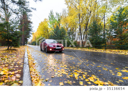 Red car on autumn road 35136654