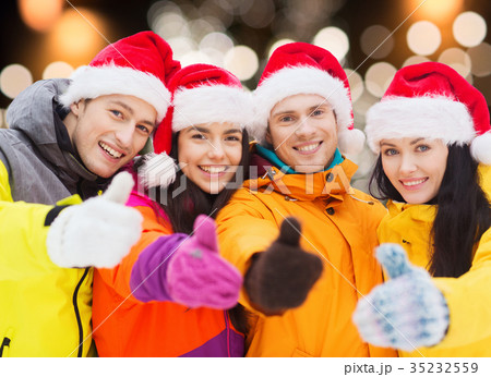 happy friends in santa hats and ski suits outdoors 35232559