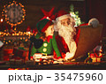 santa claus reads list of good children to little elf by Christm 35475960