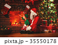 Merry Christmas! Santa Claus and little elf near   fireplace 35550178