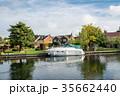 イギリス郊外の運河に停泊するボートと運河脇にある豪邸と黄色に色づく大木 35662440