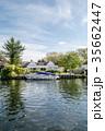 イギリス郊外の運河に停泊するボートと運河脇にある豪邸と黄色に色づく大木 35662447