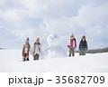 雪だるまの周りで微笑む小学生 35682709