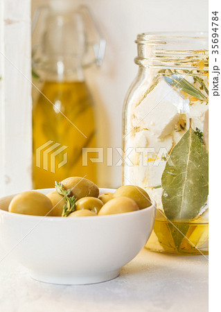 Green olives, feta cheese with olive oil in a jarの写真素材 [35694784] - PIXTA