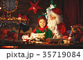 santa claus reads letter to little elf by Christmas tree 35719084