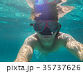 A man with an underwater mask swims in the Sea 35737626