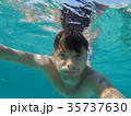 A man swims in the sea is engaged in diving 35737630