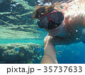 A man with an underwater mask swims near the corals in the Sea 35737633