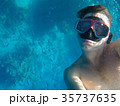 A man with an underwater mask swims near the corals in the Sea 35737635