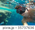 A man with an underwater mask swims near the corals in the Sea 35737636