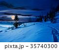 rural footpath through snowy hillside at night 35740300
