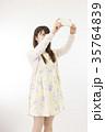 人物 女性 20代 白背景 スマホ ニーショット 縦 自撮り 35764839