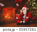 santa claus reads a book to a little elf by Christmas tree 35957261
