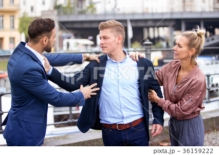 two men fighting while a woman...