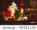 santa claus reads letter to little elf by Christmas tree 36161143