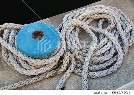 岸壁でとぐろを巻く長いロープと係船柱(繋留用のボラード)。 36317915