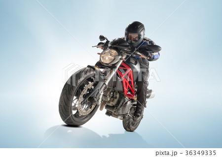 Biker in black jacket and helmet sitting on his 36349335