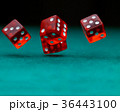 Photo of several red dice falling on green table 36443100