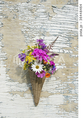 wicker basket on old wooden wall with flowersの写真素材 [36448464] - PIXTA