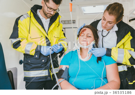 Medics taking care of inured woman in ambulance 36535186
